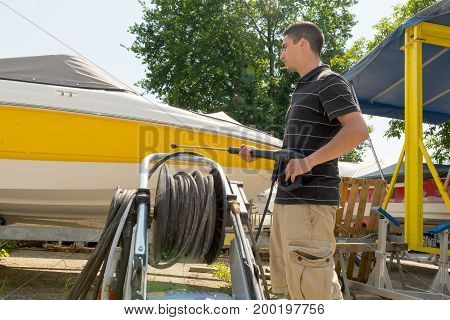 a young man cleaning boat with high pressure water