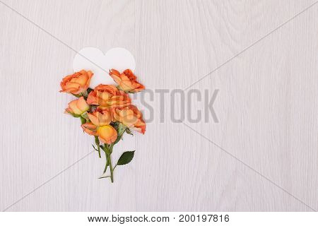 Creative mock up layout made of roses  with copy space on table homemade flat lay. Empty sheet of heart card. a blank piece of paper. ribbon
