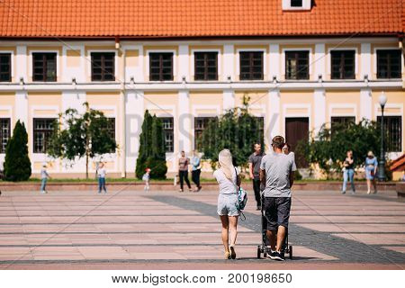Grodno, Belarus - June 11, 2017: Young Family Couple With A Stroller Walking Near Old House Of Vice - Administrator In Sunny Summer Day In Hrodna, Belarus