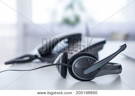 Communication support call center and customer service help desk. VOIP headset on laptop computer keyboard.