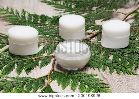 Beauty from nature concept. Fresh green leaves on shabby wooden surface with jars of moisturizing creams