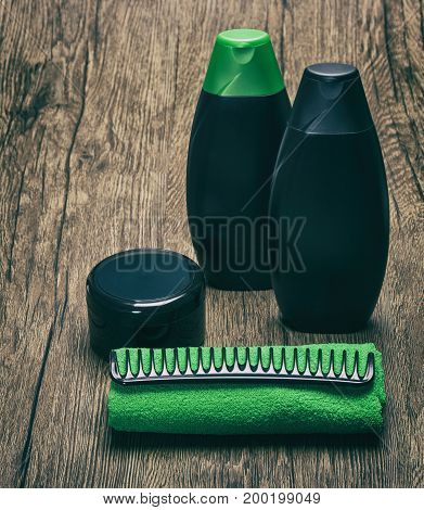 Hair care cosmetics. Shampoo, hair conditioner and mask with terry cloth towel and comb. Toned image with copy space