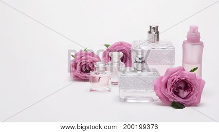 Several perfume bottles of different sizes with rose flowers on light background. Copy space
