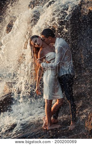 Young enamored wet couple hugs and kisses under spray and drops of waterfall. Around them are visible jets and streams of running water.