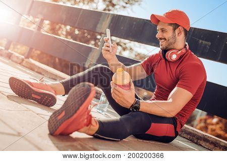 Young male jogger athlete training and doing workout outdoors in city.