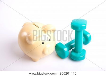 Green Dumbbells With Piggy Bank For Health Insurance Concept