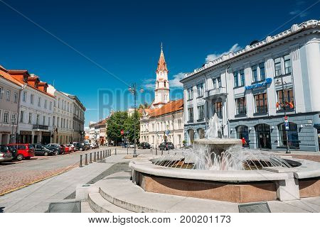 Vilnius, Lithuania - July 5, 2016: Town Hall Square Fountain In Rotuses Square In Old Town. St. Nicholas Church In Sunny Summer Day. Popular Touristic place