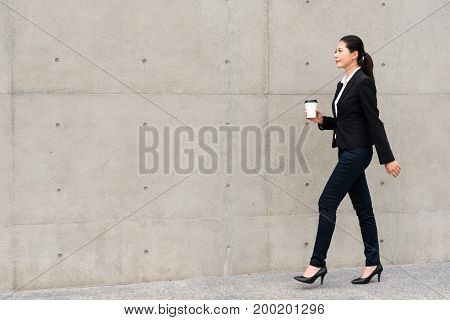 Elegant Manager Woman Walking On Gray Wall