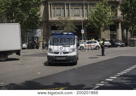 Barcelona, Spain - July 18 2017: Police van patrolling on the city center. A police car belonging to Guardia Urbana securing road safety.