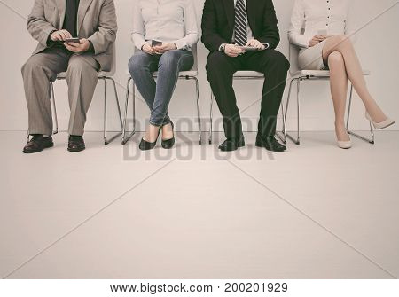 Business people waiting for job interview. Four candidates.