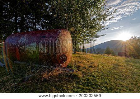 Rusty tank on green meadow. Sunrise behind the mountain.