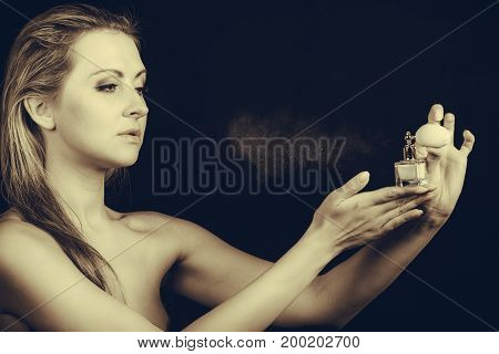 Smell elegance concept. Beautiful elegant blonde woman with necklace applying perfume after shower on naked body studio shot on dark background sepia.