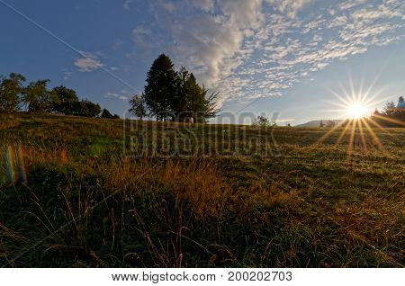 Sunrise over country meadow. Beautful clouds on the blue sky. Trees in the background. Poland.