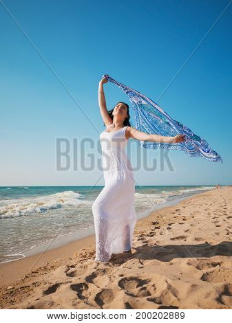 Gypsy young brunette Girl wearing white maxi long dress standing on the sea or ocean beach with mandala silk scarf in hands. Bohemian clothing style.