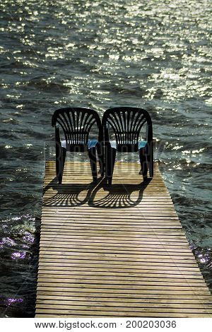 Two vacant places available, empty chairs by a lake
