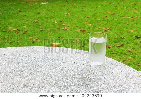 glass of water ice on terrazzo floor table with nature background and copy space add text