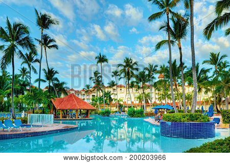 PUNTA CANA, DOMINICAN REPUBLIC, FEB. 21, 2013: Luxury Borcelo Hotels Resorts hotel swimming pool, buildings with apartments among tropical palms. Tropical holidays, vacations, tours
