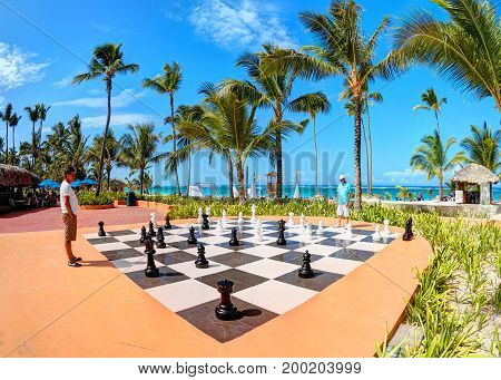 PUNTA CANA, DOMINICAN REPUBLIC, FEB. 21, 2013:  Tourists play outdoor tropical Chess on Atlantic ocean sand beach of hotel Borcelo Hotels and Resorts. Bali holidays vacations sport tours travel