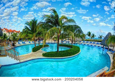 PUNTA CANA, DOMINICAN REPUBLIC, FEB,21, 2013:  Borcelo Hotels and Resorts hotel swimming pool toasted relaxing tourists on sun bads chairs palms. Punta Cana tropical holidays vacations tours travel