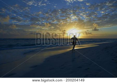 View on running man to beautiful sunset on tropical white sand beach under blue cloudy sky. Beach sports and exercise. Beach active sport - running. Man runs on sand beach