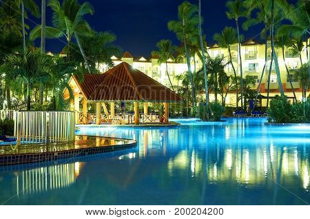 PUNTA CANA, DOMINICAN REPUBLIC, FEB. 21, 2013:  Borcelo Hotels Resorts hotel swimming pool at night lights illumination buildings with apartments among tropical palms Tropical holidays vacations tours