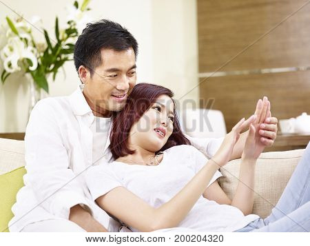 young asian couple sitting on couch and chatting at home