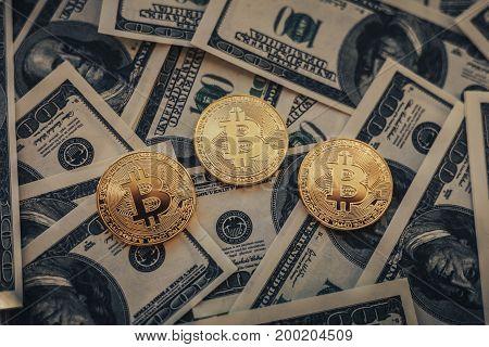 Bitcoin coins on hundred us dollars bill background, dark toned