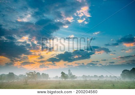 Misty Landscape. Scenic View. Morning Sunrise Sky Over Misty Meadow.  Autumn Nature Of Belarus Or European Part Of Russia. Scenic View.