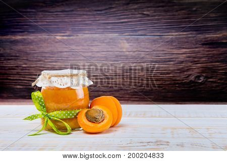 Glass Jar With Apricot Jam With Half Apricot On Wooden Background On The Kitchen Table.