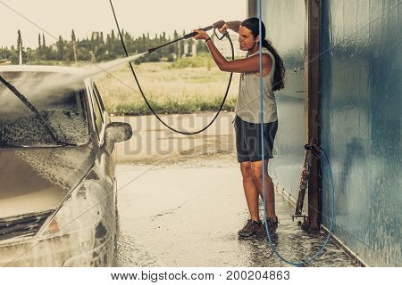 Young man cleaning his car using high pressure water in self-service car wash, toned