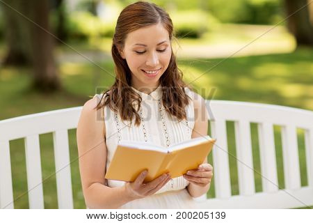 leisure, literature and people concept - smiling young woman in white dress reading book sitting on bench at summer park