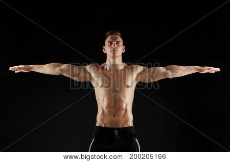 sport, bodybuilding, fitness and people concept - young man or bodybuilder with bare torso over black background