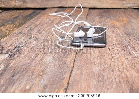 white earphone on mobile phone with table old wooden vintage background and copy space select focus with shallow depth of field