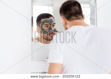 grooming, skin care and people concept - young man with brush applying clay mask at home bathroom mirror