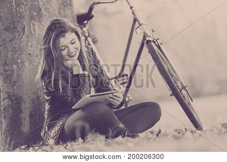 Relax leisure nature outdoor internet technology concept. Redhead lady under tree. Young girl browsing tablet resting next to bike.