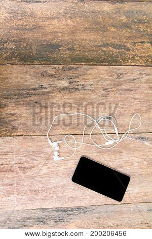 white earphone and mobile phone on table old wooden vintage background with copy space. top view