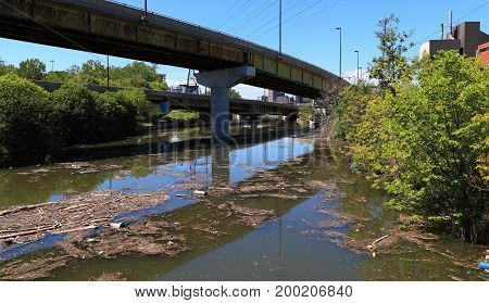 Garbage and debris pollute this waterway under an overpass.