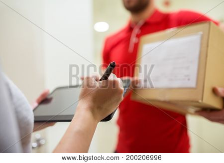 home delivery service, mail, people and shipping concept - woman customer with tablet pc computer signing for parcel box
