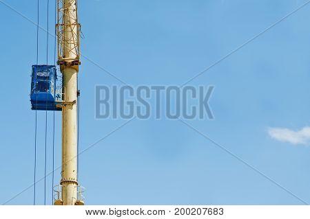 Blue Cabin On Huge Yelllow Lifting Crane.