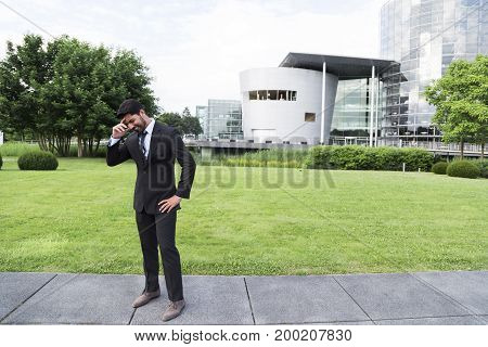 Disappointed sad unhappy businessman or worker in black suit with tie and shirt with beard standing in front of an office building with hand on his head on green grass in summer day.