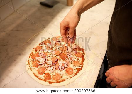 food, culinary, italian cuisine, people and cooking concept - cook hands adding red onion to salami pizza at pizzeria