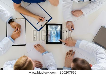 medicine, healthcare and surgery concept - group of doctors or surgeons discussing spine x-ray on tablet pc computer screen at hospital