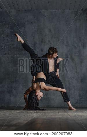 Couple of ballet dancers posing in studio