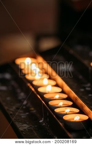 Group Of Candles In Church. Candles Light Flame At Night.