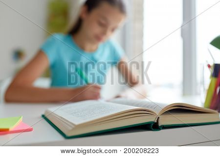 people, education and children concept - girl with book writing at home
