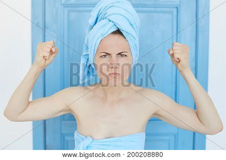 Portrait of young blue-eyed lady standing indoors with fist bunched and face screwed. Woman after shower is ready to fight, the girl is horrified and frowning her eyebrows with negative emotions