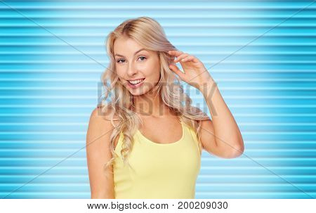 hairstyle and people concept - happy smiling beautiful young woman with blonde hair over ribbed blue background
