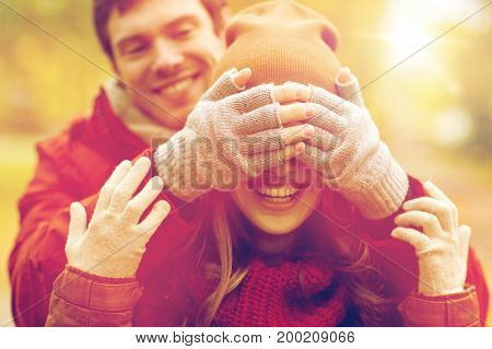 love, relationships, season and people concept - happy young couple having fun in autumn park