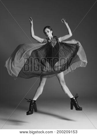 Young beautiful dancer is posing in studio