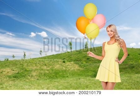 people, holidays and summer party concept - happy young woman or teen girl in yellow dress with helium air balloons over blue sky and green field background